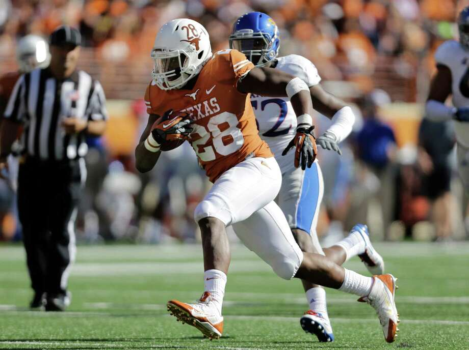 Texas' Malcolm Brown (28) is pursued by Kansas' Darius Willis (52) during the first half of an NCAA college football game, Saturday, Nov. 2, 2013, in Austin, Texas. (AP Photo/Eric Gay) Photo: Eric Gay, Associated Press / AP