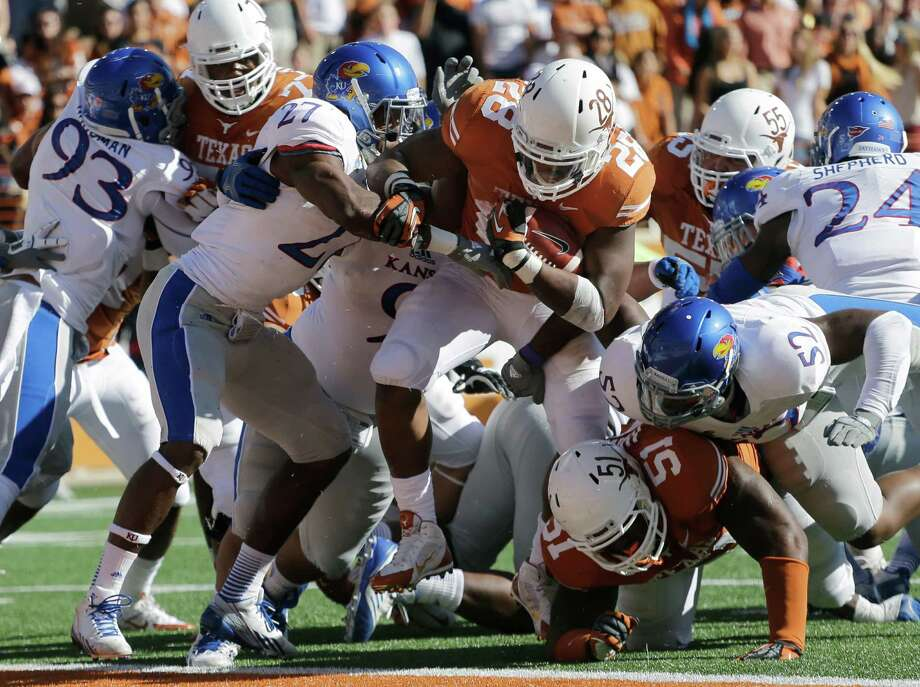 Texas' Malcolm Brown (28) scores against Kansas during the first half of an NCAA college football game, Saturday, Nov. 2, 2013, in Austin, Texas. (AP Photo/Eric Gay) Photo: Eric Gay, Associated Press / AP