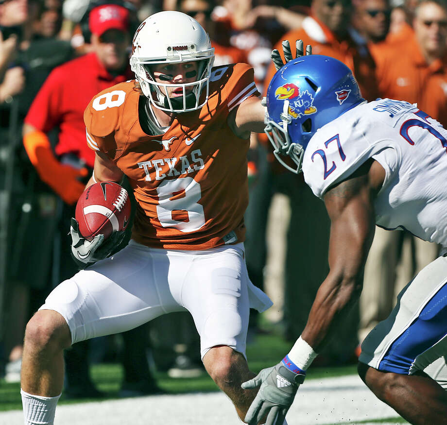 Jaxon Shipley extends a stiff arm toward Victor Simmons who caught up with after the TExas receiver stumbled on a long catch in the first half as Texas hosts Kansas at Darrell K. Royal Stadium  on November 2, 2013. Photo: TOM REEL, San Antonio Express-News