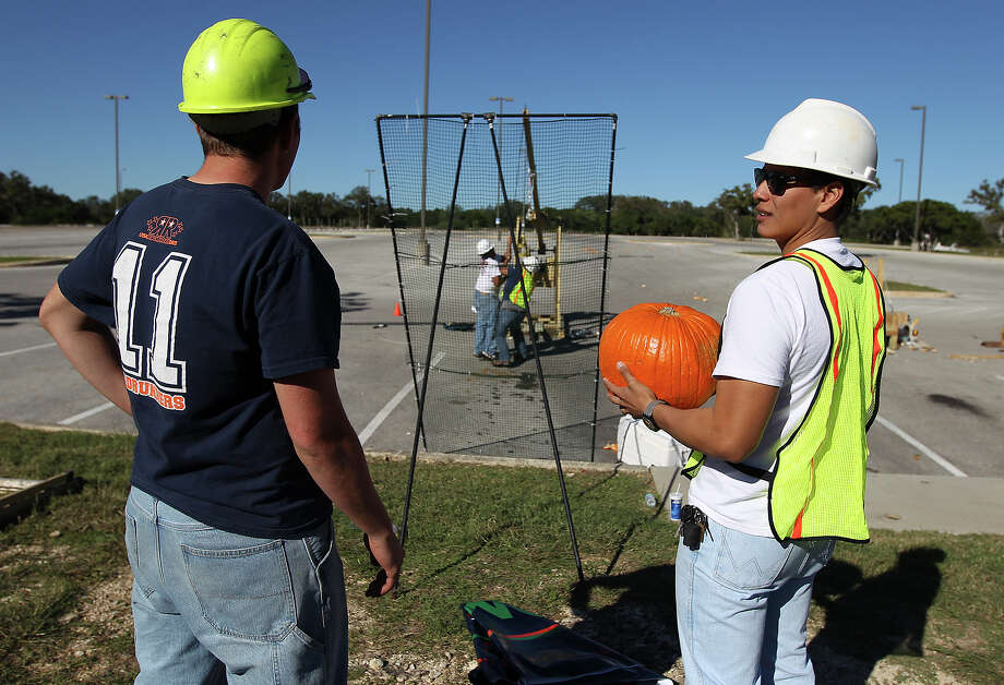 UTSA students Joseph Medrano (right) holds onto a pumpkin as he and teammate Nathan Itz await for their trebuchet to be set for launch during the school's popular Monster Mash Pumpkin Smash in conjunction with STEM Fest on Saturday, Nov. 2, 2013. The event challenged students to design and build a trebuchet or catapult that could best launch an object like a pumpkin. The event was open to the public. Photo: Kin Man Hui, San Antonio Express-News / ©2013 San Antonio Express-News