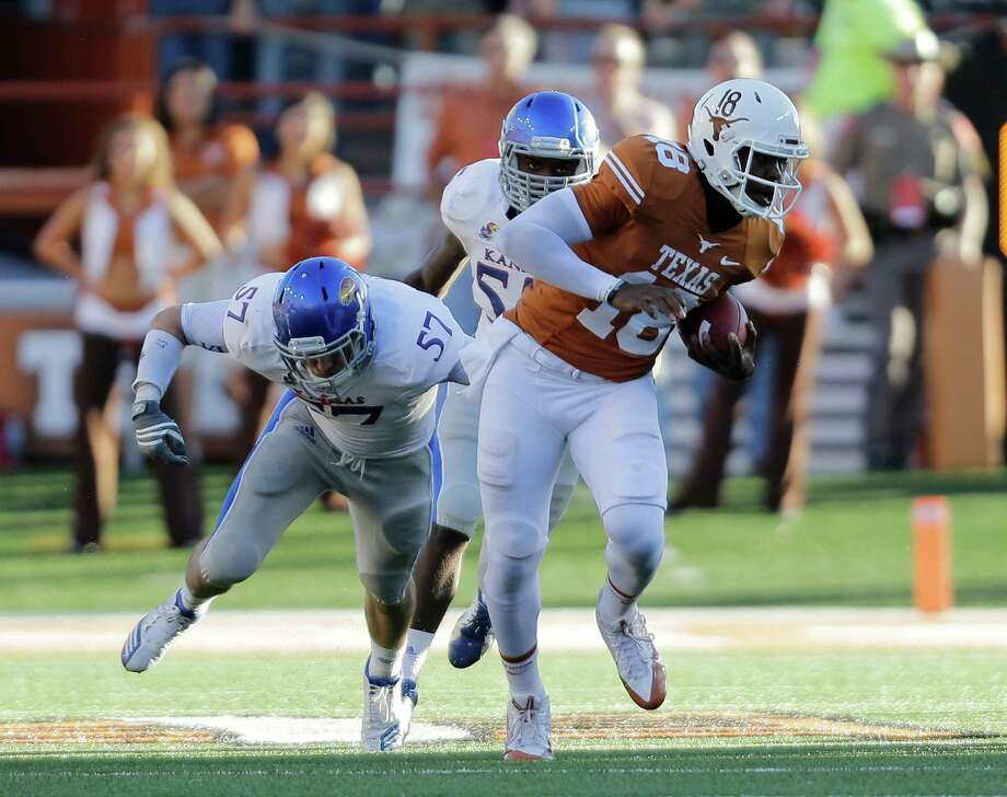 Texas' Tyrone Swoopes (18) tries to escape from Kansas defender Jake Love (57) during the second half of an NCAA college football game, Saturday, Nov. 2, 2013, in Austin, Texas. Texas won 35-13. (AP Photo/Eric Gay) Photo: Eric Gay, Associated Press / AP
