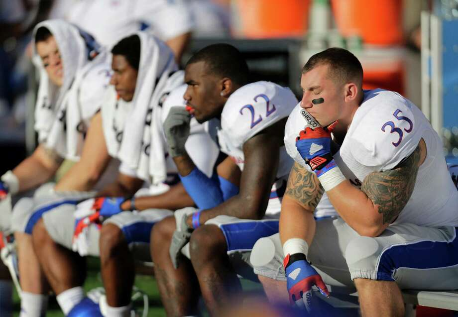 Kansas' Greg Allen (22),T.J. Semke (35) and other players sit on the bench during the final moments of the team's 35-13 loss to Texas during an NCAA college football game, Saturday, Nov. 2, 2013, in Austin, Texas. (AP Photo/Eric Gay) Photo: Eric Gay, Associated Press / AP