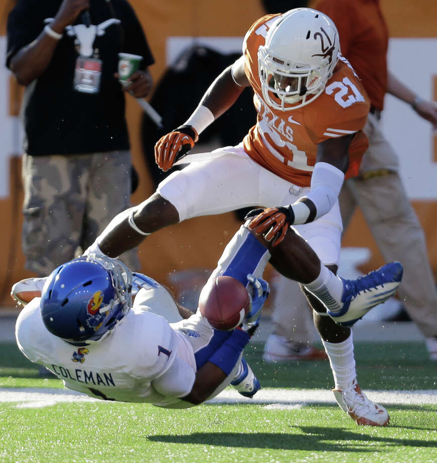 Kansas' Rodriguez Coleman (1) bobbles a pass as Texas' Duke Thomas (21) defends during the second half of an NCAA college football game, Saturday, Nov. 2, 2013, in Austin, Texas. The pass was incomplete. Texas won 35-13. (AP Photo/Eric Gay) Photo: Eric Gay, Associated Press / AP