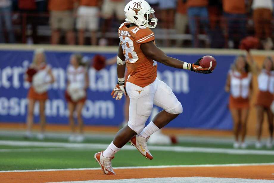 Texas' Malcolm Brown scores a touchdown against Kansas during the second half of an NCAA college football game, Saturday, Nov. 2, 2013, in Austin, Texas. Texas won 35-13. Brown ran for 119 yards and scored four touchdowns. (AP Photo/Eric Gay) Photo: Eric Gay, Associated Press / AP