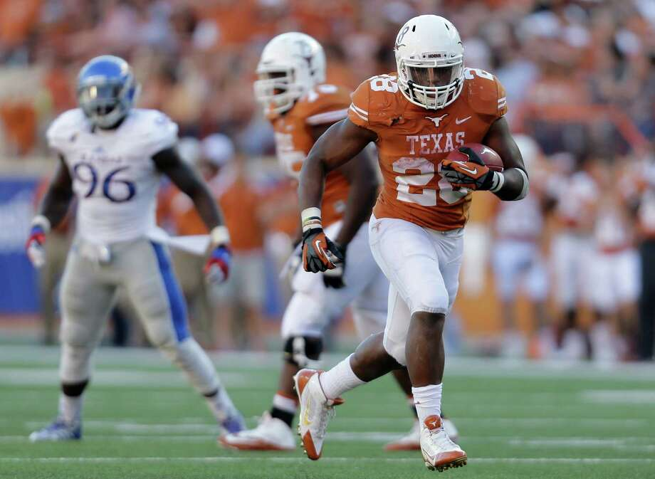 Texas' Malcolm Brown (28) breaks for a touchdown run against Kansas during the second half of an NCAA college football game, Saturday, Nov. 2, 2013, in Austin, Texas. Texas won 35-13. Brown ran for 119 yards and scored four touchdowns. (AP Photo/Eric Gay) Photo: Eric Gay, Associated Press / AP