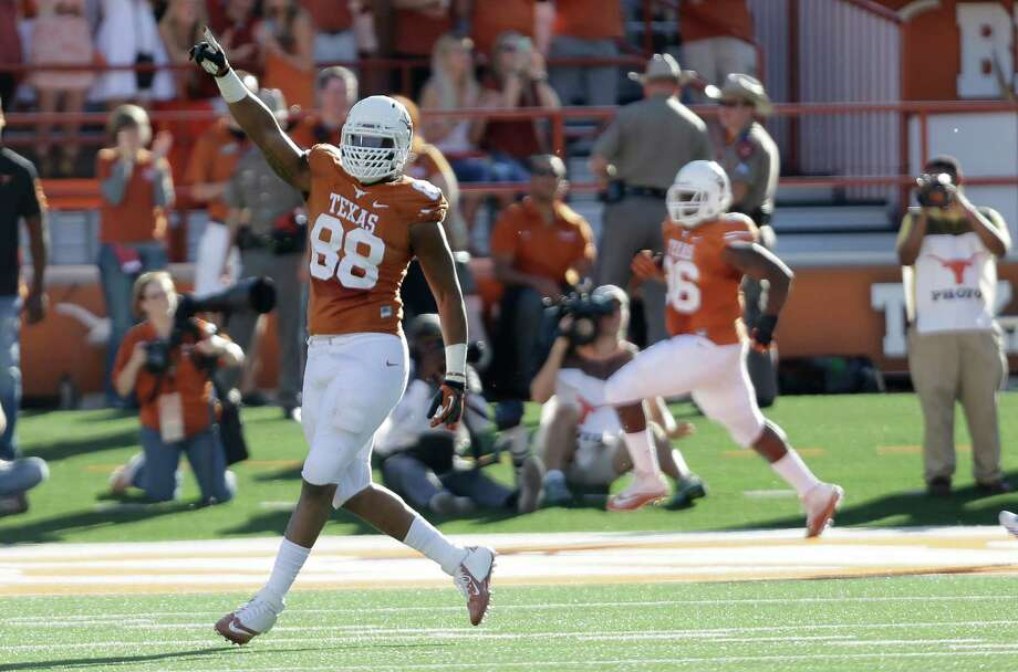 Texas' Cedric Reed (88) celebrates as teammate Chris Whaley (96) returns a fumble for a touchdown against Kansas during the second half of an NCAA college football game, Saturday, Nov. 2, 2013, in Austin, Texas. Texas won 35-13. (AP Photo/Eric Gay) Photo: Eric Gay, Associated Press / AP