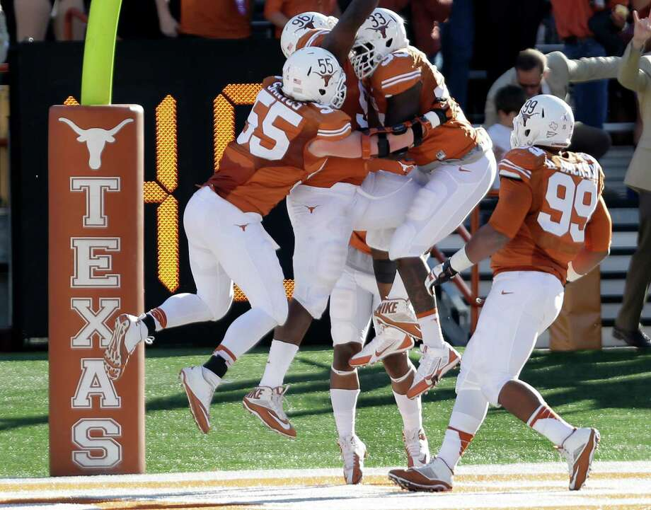 Texas' Chris Whaley (96) celebrates with teammates after he returned a Kansas fumble for a touchdown during the second half of an NCAA college football game, Saturday, Nov. 2, 2013, in Austin, Texas. Texas won 35-13. (AP Photo/Eric Gay) Photo: Eric Gay, Associated Press / AP