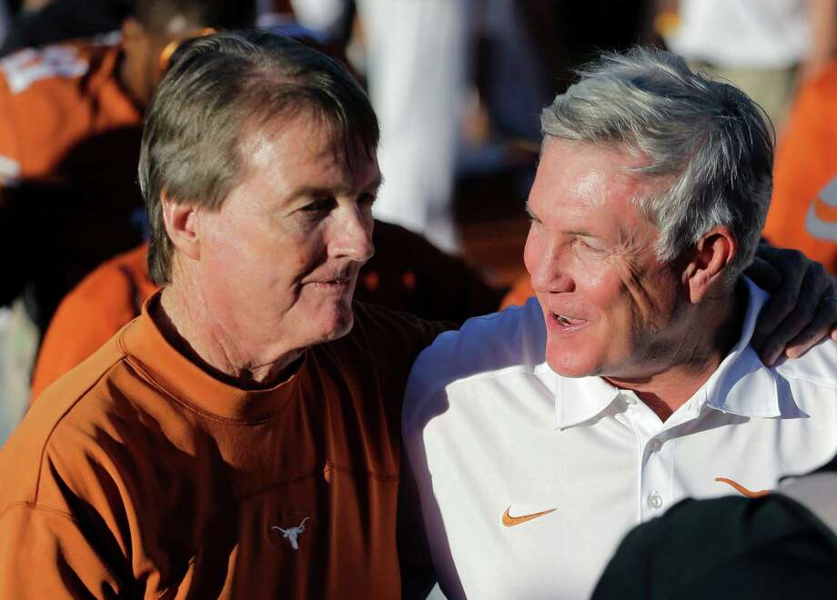 Texas coach Mack Brown, right, walks off the field with university president Bill Powers, left, after Texas' 35-13 win over Kansas in an NCAA college football game, Saturday, Nov. 2, 2013, in Austin, Texas. (AP Photo/Eric Gay) Photo: Eric Gay, Associated Press / AP