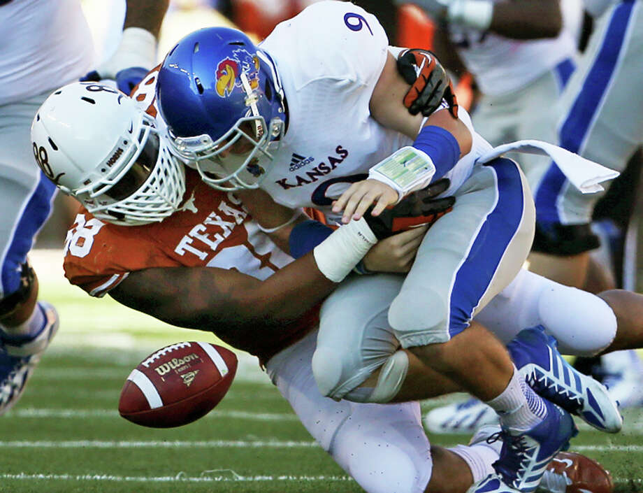 Montrel Meander forces Jayhawk quarterback Jake Heaps to fumble, resulting in fellow lineman Chris Whaley getting a touchdown as Texas hosts Kansas at Darrell K. Royal Stadium  on November 2, 2013. Photo: TOM REEL, San Antonio Express-News