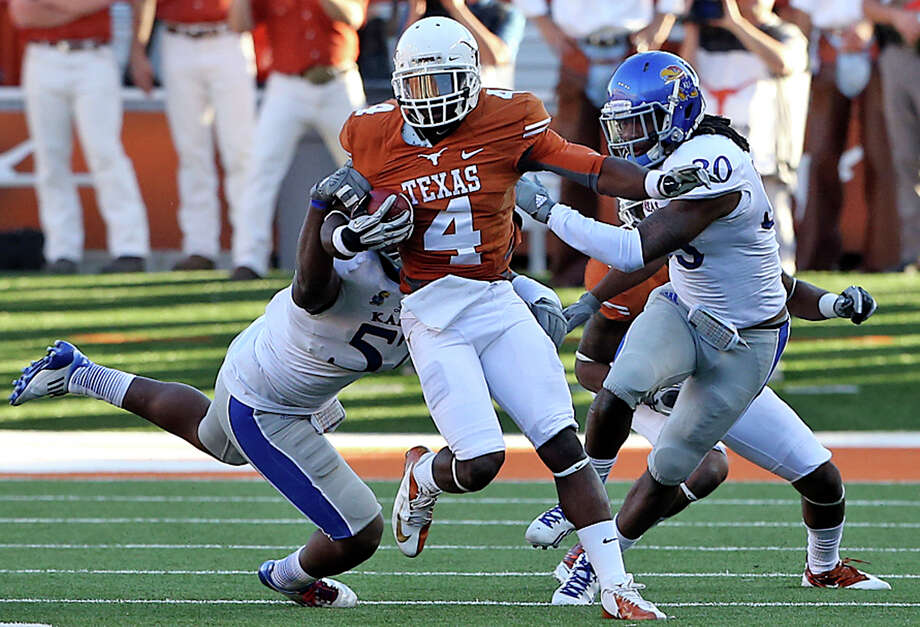 Longhorn return specialist Daje Johnson breaks a tackle as Texas hosts Kansas at Darrell K. Royal Stadium  on November 2, 2013. Photo: TOM REEL, San Antonio Express-News