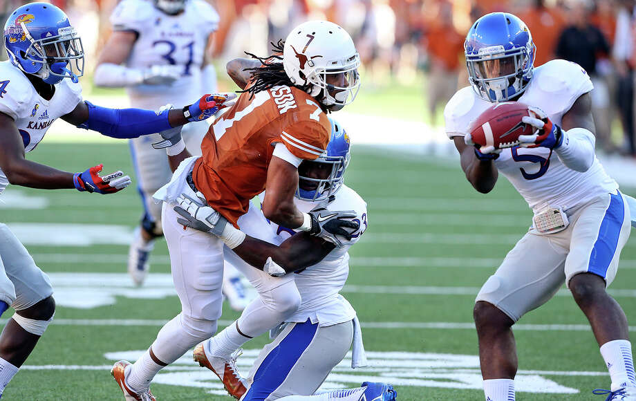 Jayhawk defender Isaiah Johnson grabs the ball intended for Marcus Johnson as Texas hosts Kansas at Darrell K. Royal Stadium  on November 2, 2013. Photo: TOM REEL, San Antonio Express-News