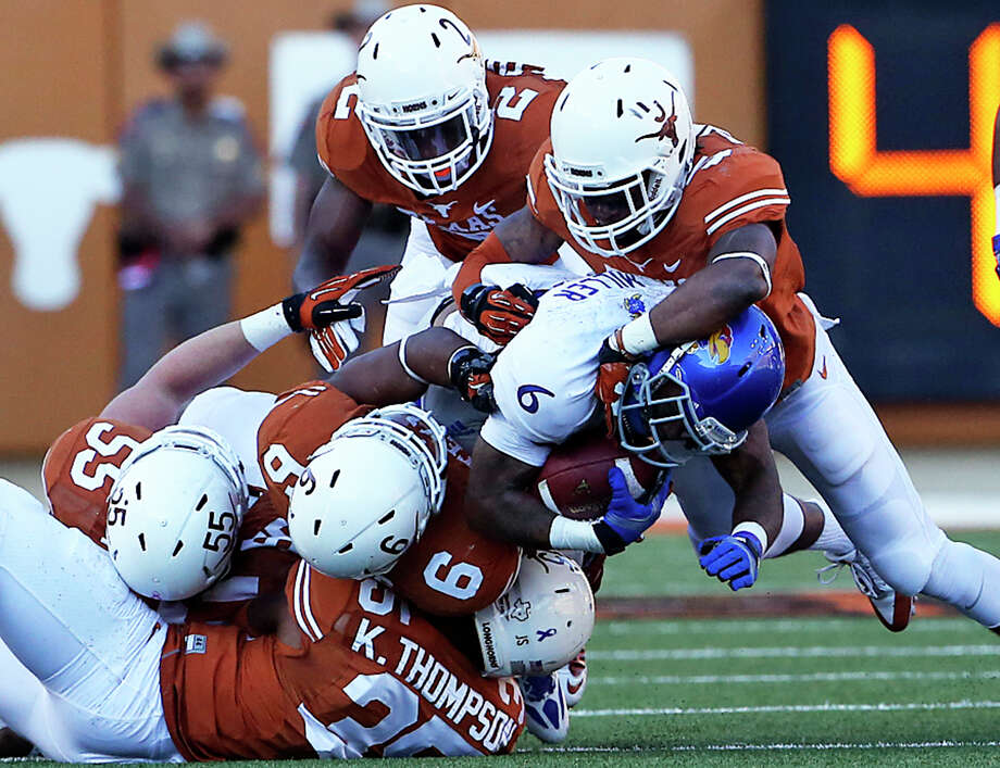 The Longhorn defense racks up halfback Darrian Miller as Texas hosts Kansas at Darrell K. Royal Stadium  on November 2, 2013. Photo: TOM REEL, San Antonio Express-News