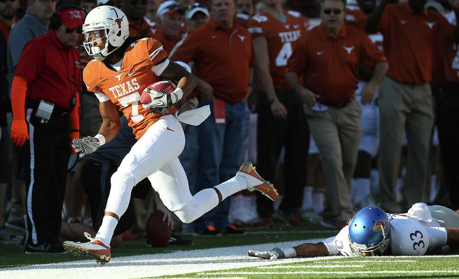 Longhorn receiver Marcus Johnson pulls down a long throw from Case McCoy in the second half in front of Cassius Sendish as Texas hosts Kansas at Darrell K. Royal Stadium  on November 2, 2013. Photo: TOM REEL, San Antonio Express-News