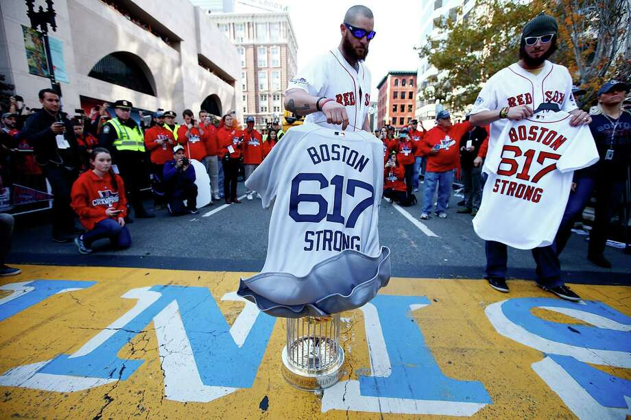 BOSTON, MA - NOVEMBER 02:  Jonny Gomes #5 and Jarrod Saltalamacchia #39 of the Boston Red Sox lay the World Series trophy and the 'Boston Strong 617' jerseys onto the finish line of the Boston Marathon on Boylston Street during the World Series victory parade on November 2, 2013 in Boston, Massachusetts. Photo: Jared Wickerham, Getty Images / Getty Images
