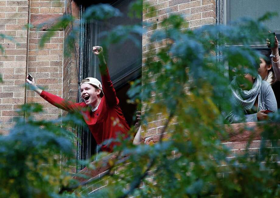 BOSTON, MA - NOVEMBER 02:  Boston Red Sox fans cheer from a window during the World Series victory parade on November 2, 2013 in Boston, Massachusetts. Photo: Jared Wickerham, Getty Images / Getty Images