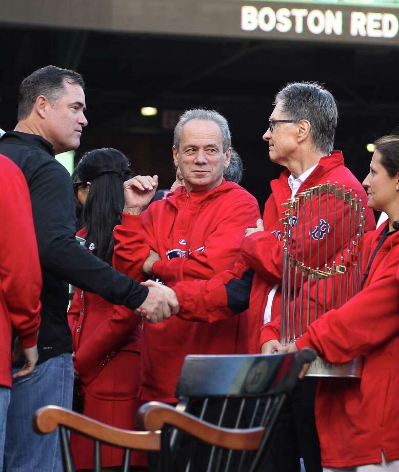 BOSTON, MA - NOVEMBER 2:  Red Sox Manager John Farrell (L) shakes hands with Red Sox principal own John Henry (right) as President and CEO of the Boston Red Sox Larry Lucchino (center) looks on as Farrell leaves the stage at Fenway Park before the Red Sox players board the duck boats for the World Series victory parade for the Boston Red Sox on November 2, 2013 in Boston, Massachusetts. Photo: Gail Oskin, Getty Images / Getty Images