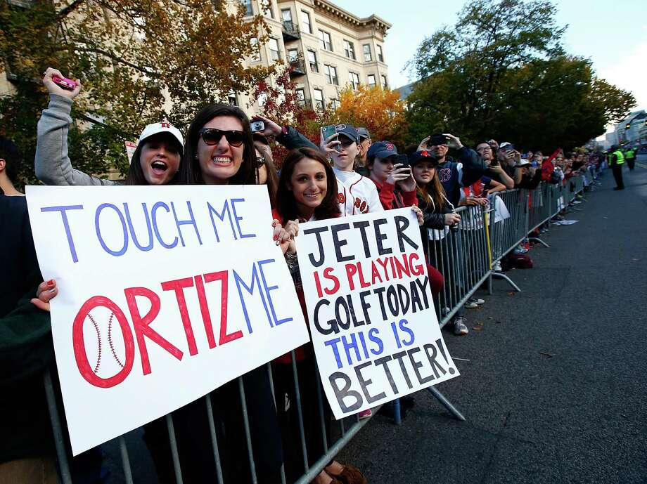 BOSTON, MA - NOVEMBER 02: Fans hold up signs during the World Series victory parade on November 2, 2013 in Boston, Massachusetts. Photo: Jared Wickerham, Getty Images / Getty Images