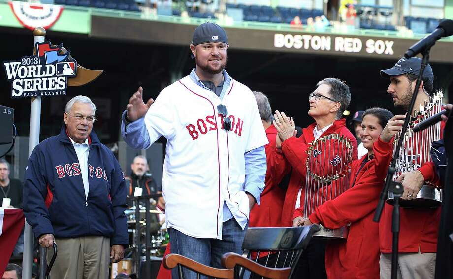 BOSTON, MA - NOVEMBER 2:  Jon Lester (center) walks on stage as Red Sox principal own John Henry (right) claps at Fenway Park before the Red Sox players board the duck boats for the World Series victory parade for the Boston Red Sox on November 2, 2013 in Boston, Massachusetts. Photo: Gail Oskin, Getty Images / Getty Images