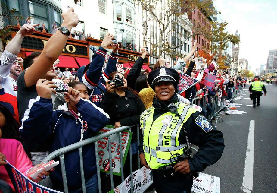 BOSTON, MA - NOVEMBER 02: Fans cheer next to a member of the Boston Police Department during the World Series victory parade on November 2, 2013 in Boston, Massachusetts. Photo: Jared Wickerham, Getty Images / Getty Images