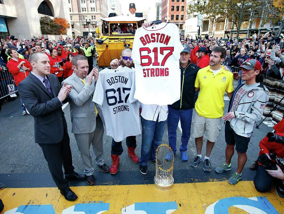 BOSTON, MA - NOVEMBER 02:  Jonny Gomes #5 and Jarrod Saltalamacchia #39 of the Boston Red Sox present the 'Boston Strong 617' jerseys to owners of two of the businesses at the bombing sites, including Shane O'Hara (second from right) and Dan Solo (R) on the finish line of the Boston Marathon on Boylston Street during the World Series victory parade on November 2, 2013 in Boston, Massachusetts. Photo: Jared Wickerham, Getty Images / Getty Images