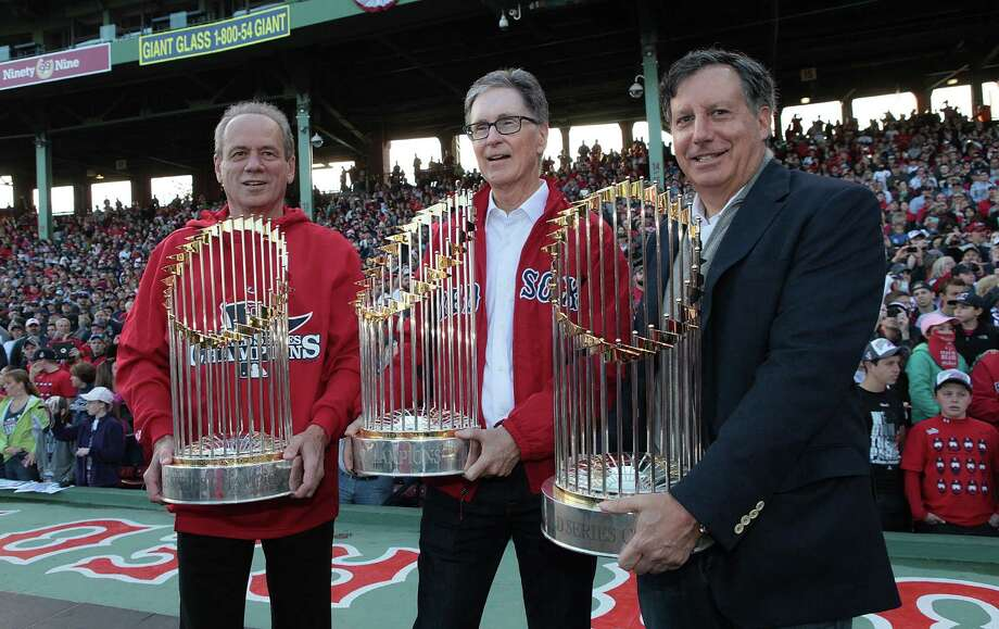 BOSTON, MA - NOVEMBER 2:  President and CEO of the Boston Red Sox Larry Lucchino, (left), Red Sox principal own John Henry (center), and Red Sox chairmanTom Werner show off the World Series trophies to the crowd at Fenway Park before the Red Sox players board the duck boats for the World Series victory parade for the Boston Red Sox on November 2, 2013 in Boston, Massachusetts. Photo: Gail Oskin, Getty Images / Getty Images