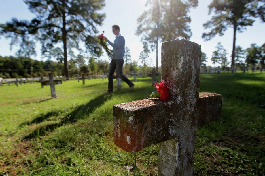 Texas Interfaith Center for Public Policy and friends and supporters lay flowers on more than 3,000 graves at Capt. Joe Byrd Cemetery on Saturday  in Huntsville. Photo: James Nielsen, Staff / © 2013  Houston Chronicle