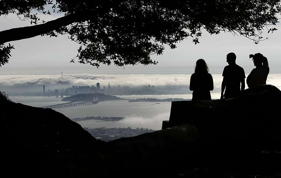 A file photo of people watching fog rolls across the San Francisco skyline and into San Francisco Bay as seen from Grizzly Peak Blvd. in Berkeley. A couple sitting in a car at a a pull-out along the road where robbed early Thursday morning. Photo: Michael Macor, The Chronicle