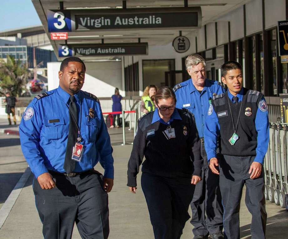 Transportation Security Administration employees wear black ribbons over their badges on Saturday, Nov. 2, 2013, at Los Angeles International Airport. A gunman armed with a semi-automatic rifle opened fire at the airport on Friday, killing a Transportation Security Administration employee and wounding two other people in an attack that frightened passengers and disrupted flights nationwide. (AP Photo/Ringo H.W. Chiu) ORG XMIT: CARC107 Photo: Ringo H.W. Chiu / FR170512 AP
