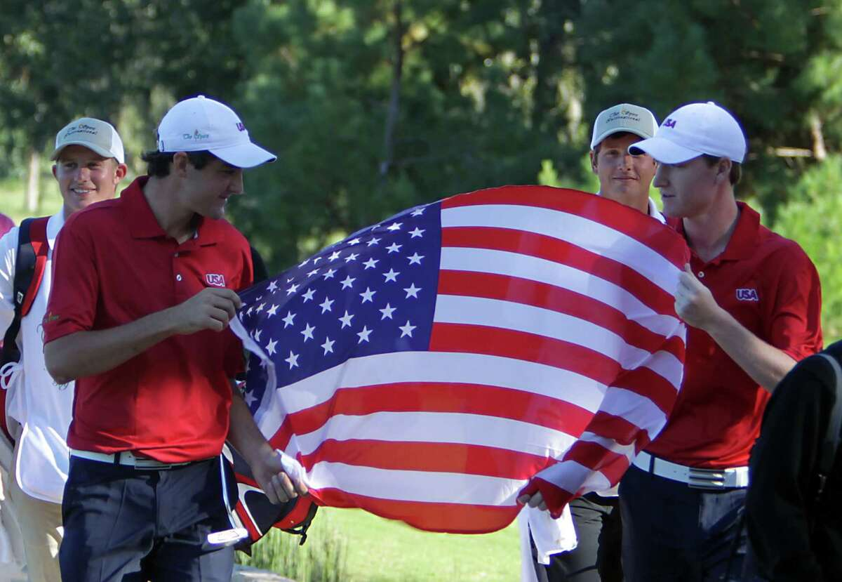 United States' Scottie Scheffler left, and teammate Jordan Niebrugge right, carry an American flag towards the 18th green during the final-round of the Spirit International golf tournament at Whispering Pines Golf Club Saturday, Nov. 2, 2013, in Trinity.