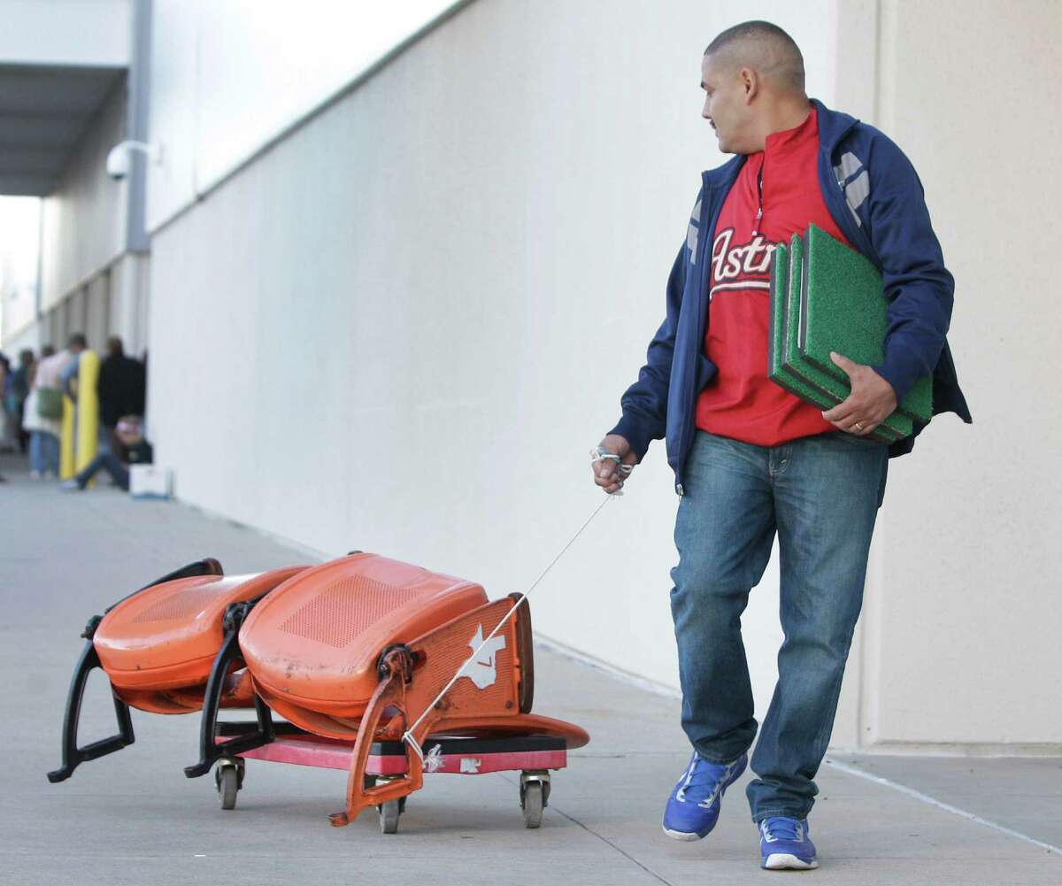 Ramon Lopez pulls a pair of seats and carries Astrodome turf he purchased during the sale at Reliant Center of Astrodome items Saturday, Nov. 2, 2013, in Houston.