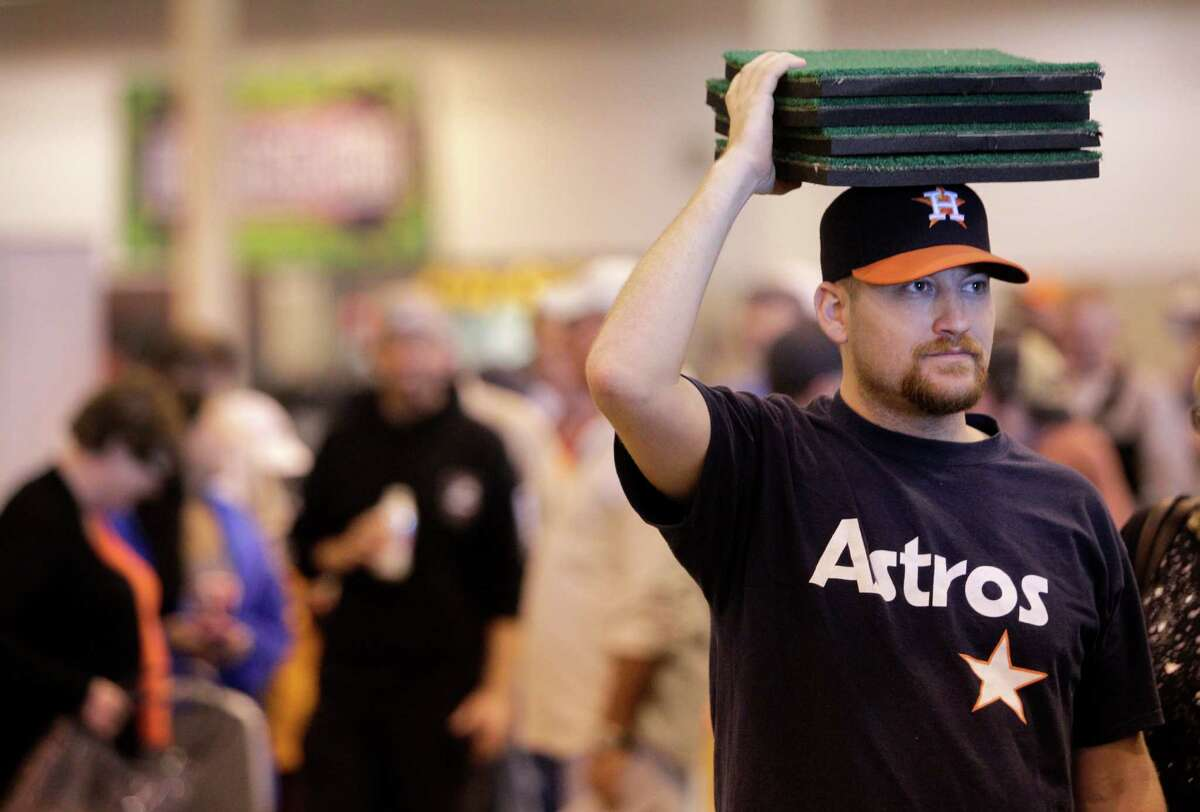 Steve Anderson, of League City, holds pieces of Astrodome turf on his head while he waits in line to buy a seat during sale of Astrodome items at Reliant Center Saturday, Nov. 2, 2013, in Houston.