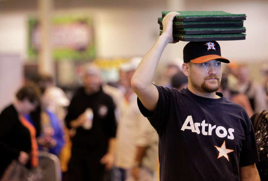 Steve Anderson, of League City, holds pieces of Astrodome turf on his head while he waits in line to buy a seat during sale of Astrodome items at Reliant Center Saturday, Nov. 2, 2013, in Houston. Photo: Melissa Phillip, Houston Chronicle / © 2013  Houston Chronicle