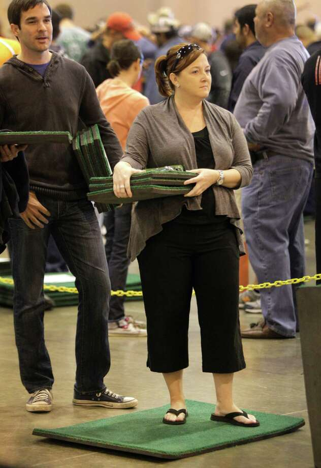 Deann Regiene stands on a 2 foot by 3 foot piece of Astrodome turf holding several 1 foot square pieces as she waits in line to buy seats during sale of Astrodome items at Reliant Center Saturday, Nov. 2, 2013, in Houston. Photo: Melissa Phillip, Houston Chronicle / © 2013  Houston Chronicle