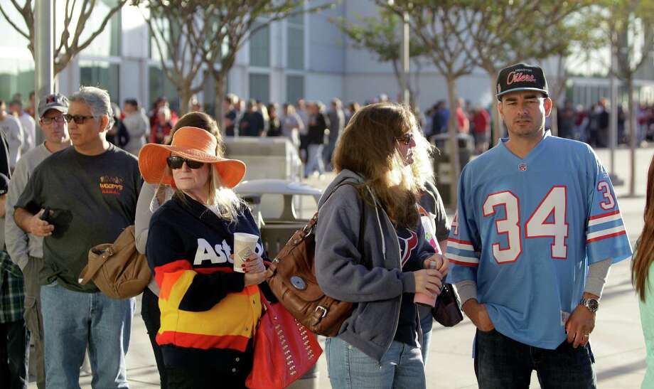 "Dene Hofheinz, second from left, whose father, the late Judge Roy Hofheinz, was the mastermind behind the Astrodome, stands in line with other fans including Leon Barrera, right, wearing an Oiler's Earl Campbell jersey, as they wait outside to enter into Reliant Center for the sale and auction of Dome seats, turf and other items Saturday, Nov. 2, 2013, in Houston. She was excited by the turn out. She said, ""The long line just keeps going on and on, it gives me goosebumps."" Photo: Melissa Phillip, Houston Chronicle / © 2013  Houston Chronicle"