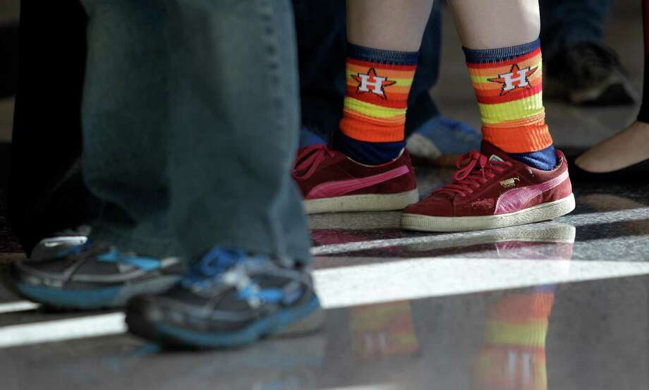 Elizabeth Eicher of Houston wears a pair of Astro rainbow socks as she waits in line in the Reliant Center lobby to enter for the auction and sale of Astrodome items at Reliant Center Saturday, Nov. 2, 2013, in Houston. Photo: Melissa Phillip, Houston Chronicle / © 2013  Houston Chronicle