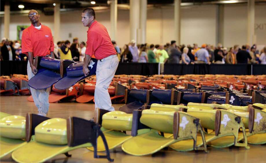 Workers carry Astrodome seats during sale of Astrodome items at Reliant Center Saturday, Nov. 2, 2013, in Houston. Photo: Melissa Phillip, Houston Chronicle / © 2013  Houston Chronicle