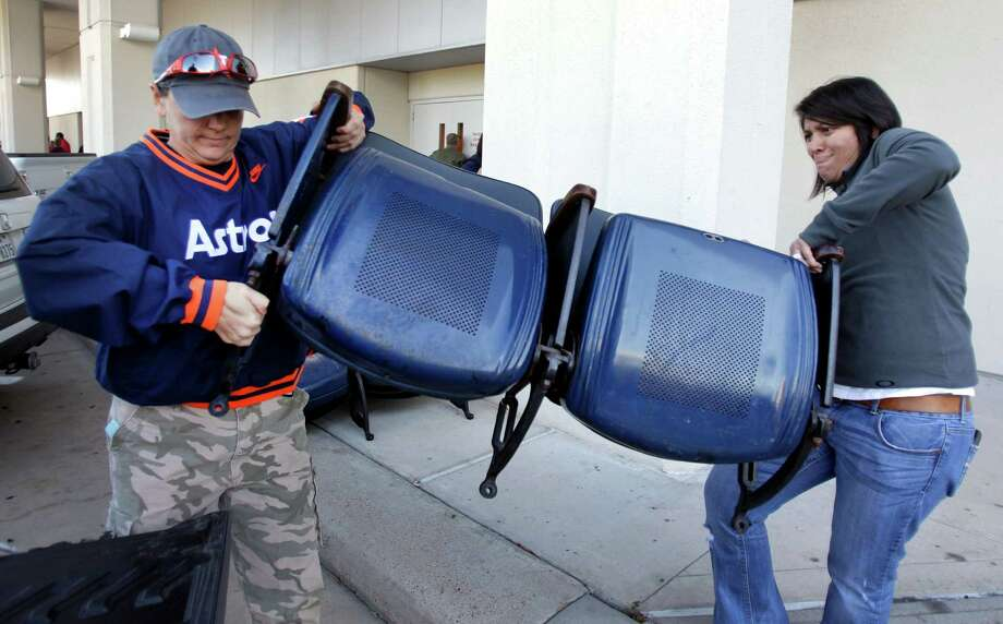 Aubrey Wadell, left, and Monica Martinez, right, load Astrodome seats they bought at sale of Astrodome items at Reliant Center Saturday, Nov. 2, 2013, in Houston. Photo: Melissa Phillip, Houston Chronicle / © 2013  Houston Chronicle