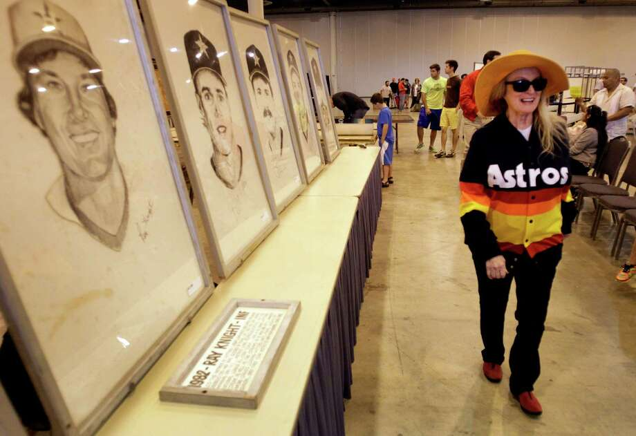 Dene Hofheinz, right, whose father, the late Judge Roy Hofheinz, was the mastermind behind the Astrodome, walks past prints of Astros players during auction and sale of Astrodome items at Reliant Center Saturday, Nov. 2, 2013, in Houston. Photo: Melissa Phillip, Houston Chronicle / © 2013  Houston Chronicle