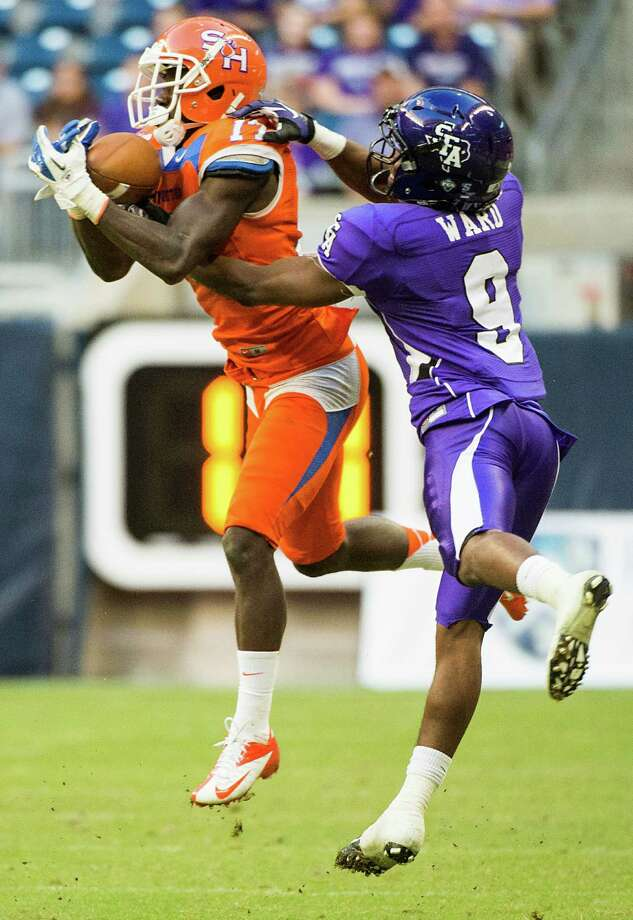 Sam Houston State cornerback Bookie Sneed intercepts a pass intended for Stephen F. Austin wide receiver DJ Ward. Photo: Smiley N. Pool, Houston Chronicle / © 2013  Houston Chronicle