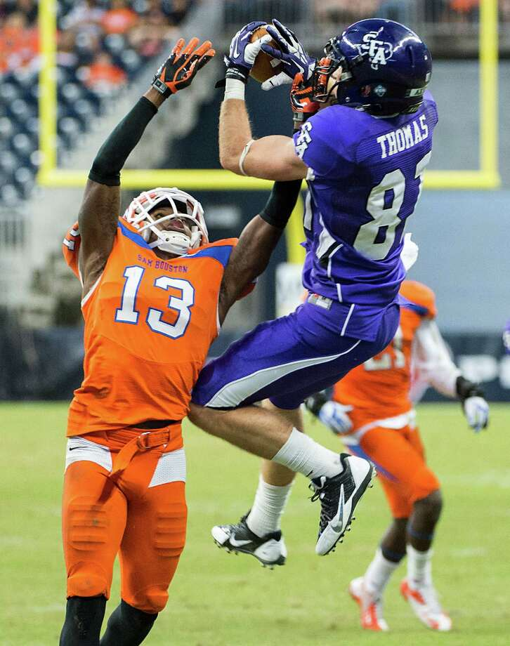 Footballs were flying all around Reliant Stadium on Saturday in a dizzying offensive display that included five receptions for 132 yards by SFA's Aaron Thomas, left. But it was Stephen Williams (82) and Torrance Williams (10) and the Bearkats who ended up on top. Photo: Smiley N. Pool, Staff / © 2013  Houston Chronicle