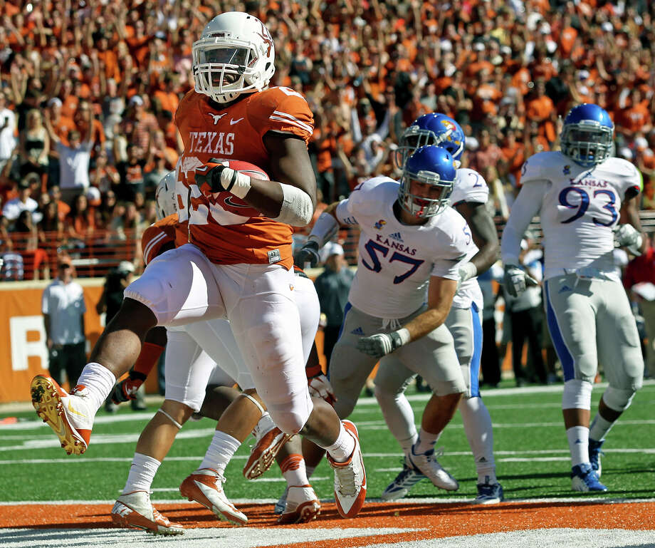 Texas' Malcolm Brown high-steps into the end zone on the first of his four touchdown runs Saturday. Brown carried 20 times for 119 yards. Photo: TOM REEL