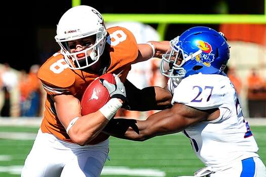 Victor Simmons #27 of the Jayhawks tackles Jaxon Shipley #8 of the Longhorns. Photo: Stacy Revere, Getty Images