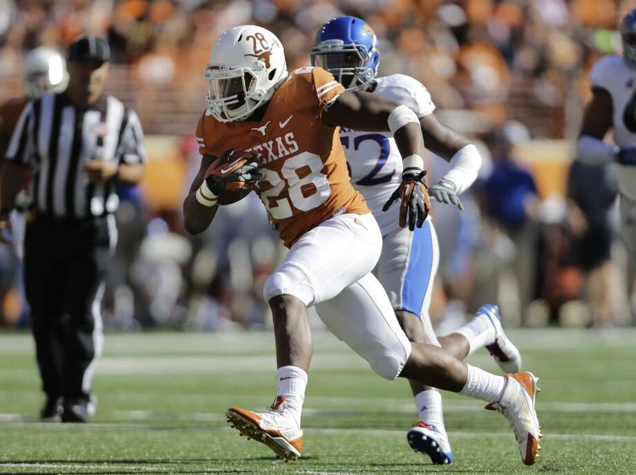 Texas' Malcolm Brown (28) is pursued by Kansas' Darius Willis (52). Photo: Eric Gay, Associated Press