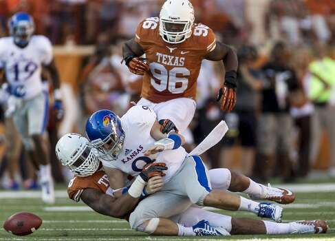 Texas' Cedric Reed sacks Kansas quarterback Jake Heaps, forcing a fumble that was recovered for a 40-yard touchdown by Chris Whaley (96). Photo: Rodolfo Gonzalez, McClatchy-Tribune News Service