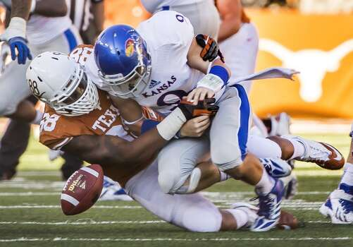 Texas' Cedric Reed (88) forces a fumble by Kansas quarterback Jake Heaps (9) in the second half. Photo: Ricardo Brazziell, McClatchy-Tribune News Service