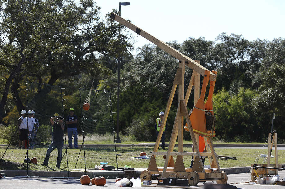 A trebuchet made by UTSA civil engineering students launches a pumpkin for the school's popular Monster Mash Pumpkin Smash in conjunction with STEM Fest on Saturday. 