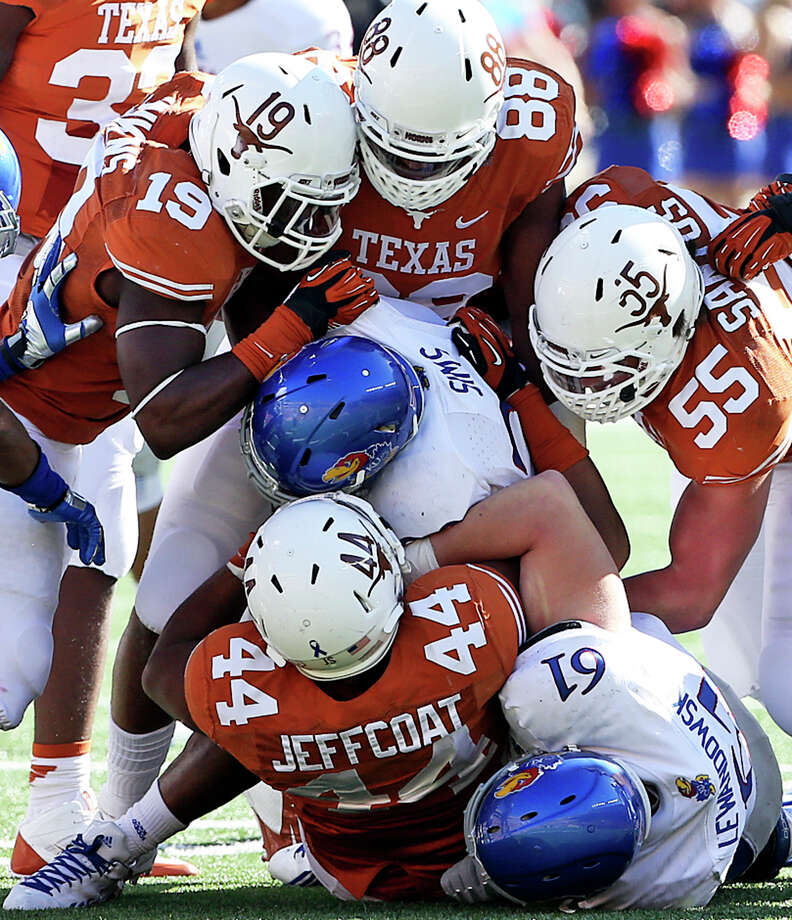 The Longhorn defense stops Jayhawk running back James Sims as Texas hosts Kansas at Darrell K. Royal Stadium  on November 2, 2013. Photo: TOM REEL, San Antonio Express-News