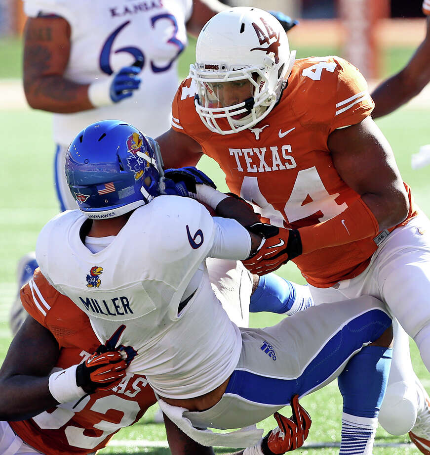 Jackson Jeffcoat combines with Steve Edmond to bring down Jayhawk halfback Darrian Miller as Texas hosts Kansas at Darrell K. Royal Stadium  on November 2, 2013. Photo: TOM REEL, San Antonio Express-News