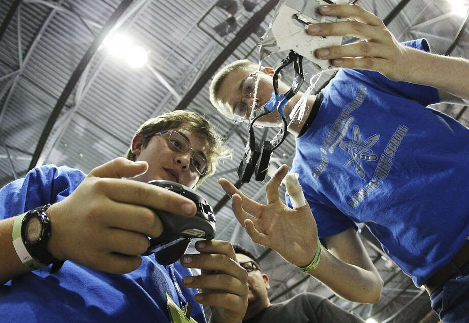 Jay High School's Alex Brown (right) and Daniel Schneider adjust their robot Saturday during the 2013 San Antonio BEST Robotics Competition. Photo: Kin Man Hui / San Antonio Express-News