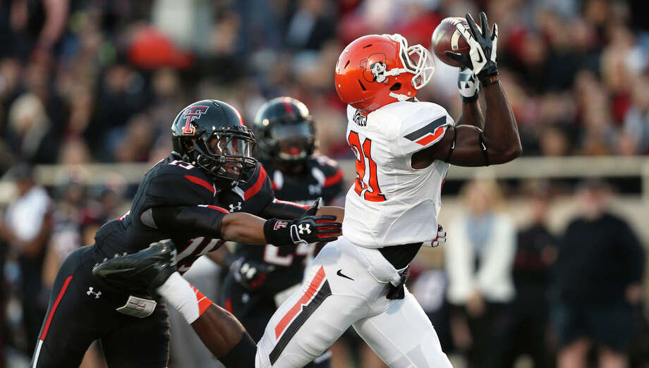 Oklahoma State's Jhajuan Seales takes an up-close look at one of his three catches. Photo: Stephen Spillman, MBI / Lubbock Avalanche-Journal